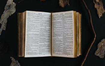 Keskeltä avattu vanha kirja, jonka sivuille on painettu paljon pientä tekstiä.